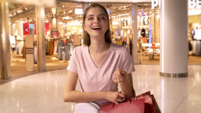 Young attractive girl goes shopping in mall, holds bags, laughing, like sign, shopping concept, fashion concept