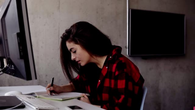 Young attractive girl in red flannel shirt writing something down in her notebook, video
