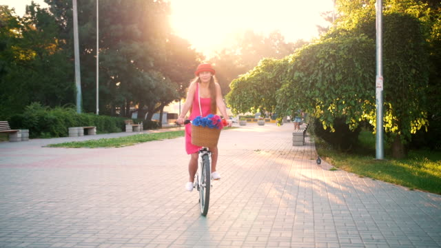 young attractive girl riding on vintage bike in park at sunset - cestino della bicicletta video stock e b–roll