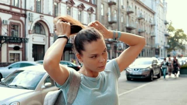 stockvideo's en b-roll-footage met jonge aantrekkelijke meisje rechtzetten haar haar in de stad in de zomer, slow motion - curly brown hair