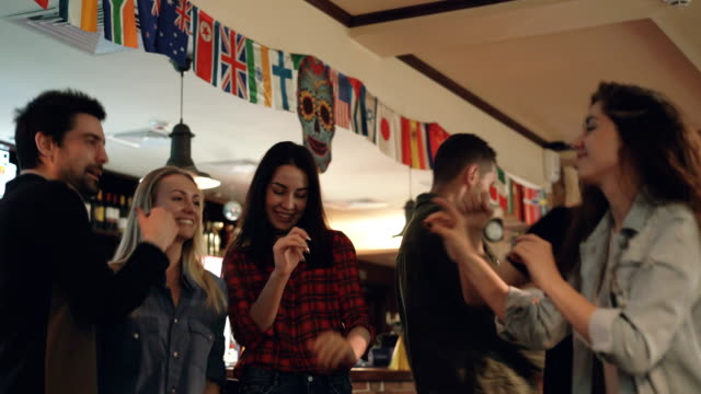 vídeos de stock e filmes b-roll de young attractive girls and guys are dancing carelessly in modern pub. beautiful people are laughing and bonding. nice bar interior and bottles with alcohol in background. - descuidado