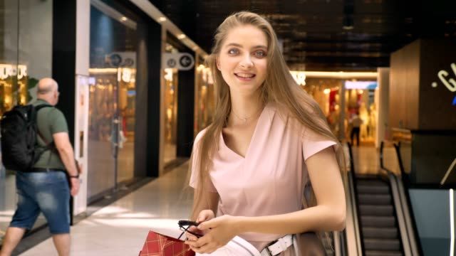 attraktiva flickor står i mall, bära väskor, titta på kameran, shopping koncept, mode koncept - köpnarkoman bildbanksvideor och videomaterial från bakom kulisserna