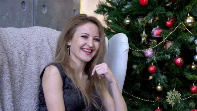 Young attractive happy woman laughing and sitting on christmas tree background. video