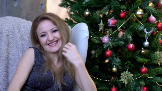 Young attractive happy woman laughing, smiling and sitting on christmas tree background. video