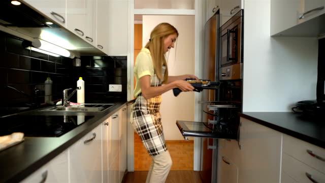 vidéos et rushes de jeune femme au foyer attractif avec gâteau chaud danse dans la cuisine - four
