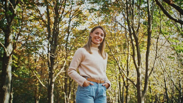 Young attractive lady smiling and looking at you while posing with her hands in pockets standing at autumn park Young attractive lady in casual outfit is smiling and looking at you while posing with her hands in pockets standing at autumn park. Sunny day, trees with yellow foliage. Slow motion, bottom up view hot pockets stock videos & royalty-free footage
