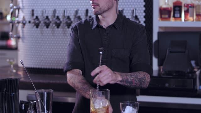 Jovem atraente barman masculino, agitando uma bebida alcoólica e coloca-lo em um copo de bebida em um bar - vídeo