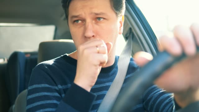 A young attractive man is coughing while driving in car A young attractive man is coughing while driving in car coughing stock videos & royalty-free footage