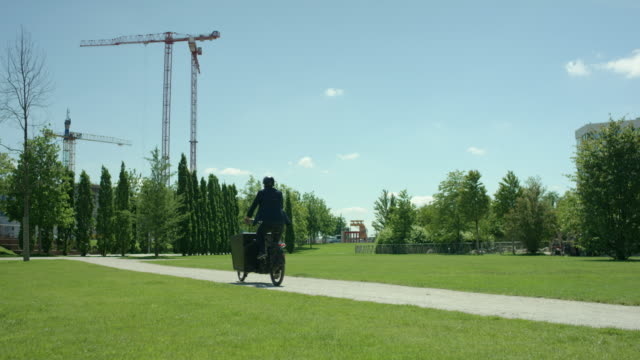 Young attractive man is riding through a green park to his work with his cargo bike video