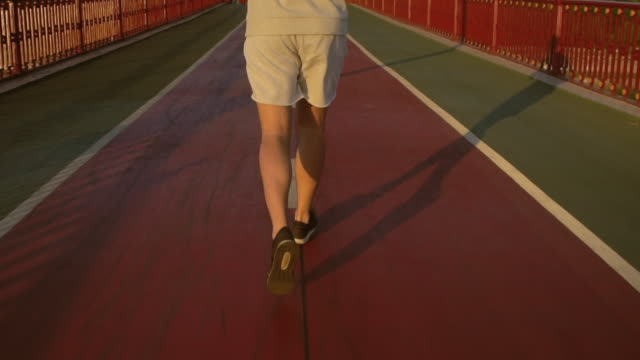 Young attractive man runs on the bridge along the river Urban runner having intensive training outdoors. Focus on legs. human back stock videos & royalty-free footage