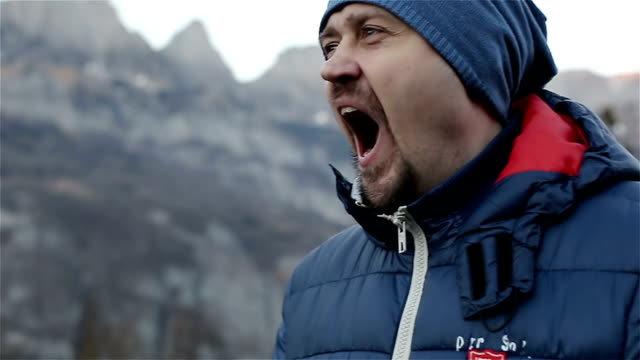 Young attractive man with beard in a cap yawns on a background of a beautiful landscape. video
