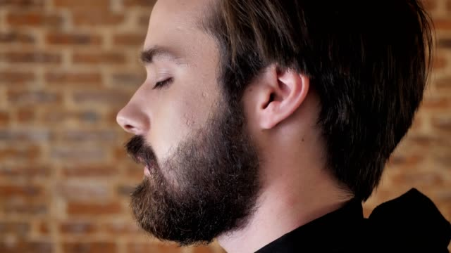 Young attractive man with beard turns head, watching at camera, smiling, flirt conception, brick background, side view video