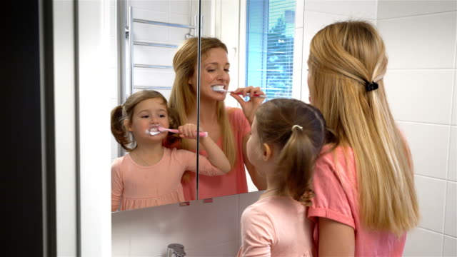 young attractive mom and her cute daughter brush their teeth. - denti video stock e b–roll