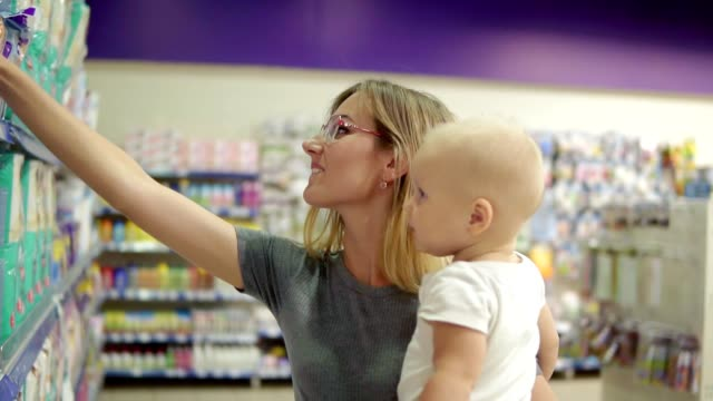 Young attractive mother in glasses holding her child in her arms while choosing diapers on the shelves in the supermarket. Thoughtful mom carefully choosing best products for her child video