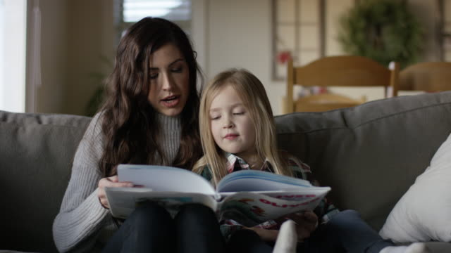 young attractive mother reading on the couch with her daughter - children video stock e b–roll