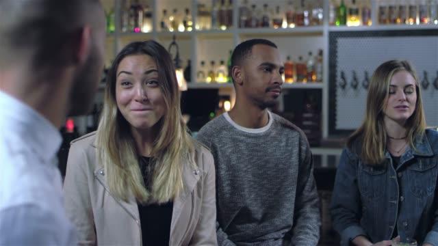 vídeos de stock, filmes e b-roll de jovens atraente as pessoas falando em um bar. os risos de jovem mulher asiática - costumer