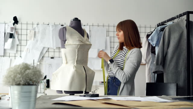 young attractive seamstress is measuring tailor's dummy with tape to make new garment with these measurements. busy day in clothing workshop concept. - designers video stock e b–roll