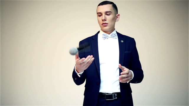 Young attractive showman staying on a stage and throwing up microphone. video