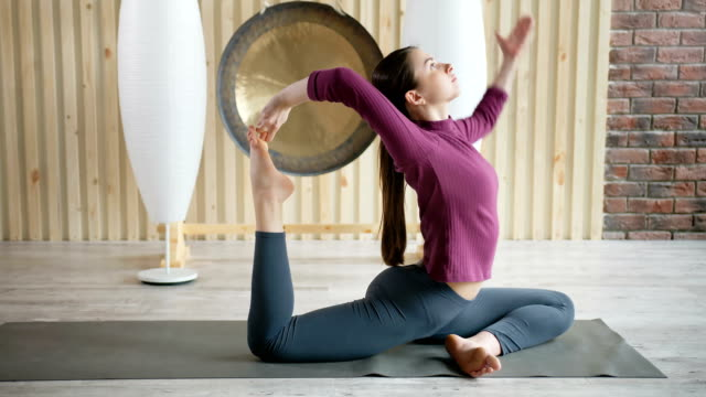 young attractive sportive woman practicing yoga, stretching in gym - metodo pilates video stock e b–roll
