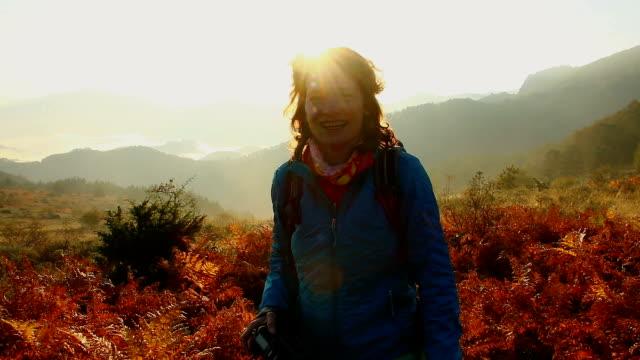 young attractive tourist woman hikes  through mountain fern fall forest and smiling to camera. steady cam shot. - attività equestre ricreativa video stock e b–roll