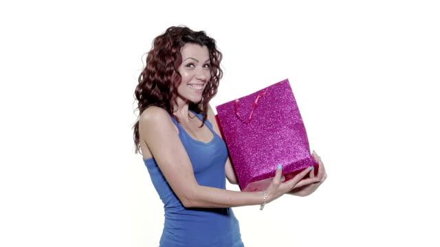 ung attraktiv kvinna fångster en presentpåse som faller från ovan - tema bildbanksvideor och videomaterial från bakom kulisserna