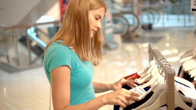 Young attractive woman choosing clothes at shop. Shopping in mall, sales time. Consumerism concept video