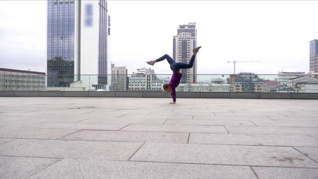 vídeos de stock, filmes e b-roll de jovem mulher atraente fazendo acrobacias com a paisagem urbana em fundo - posição