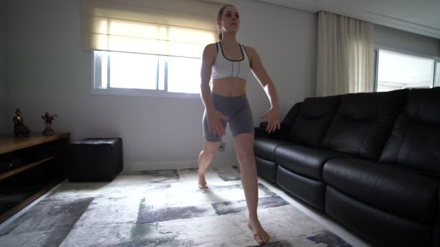 giovane donna attraente che fa allenamento a casa esibendosi - materassino ginnico video stock e b–roll