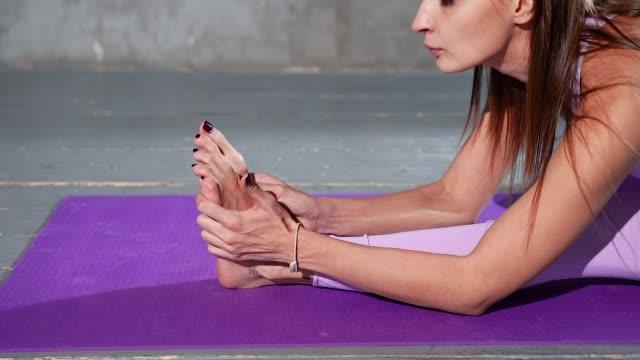 молодая привлекательная женщина делает растяжения на коврик для йоги. - class стоковые видео и кадры b-roll