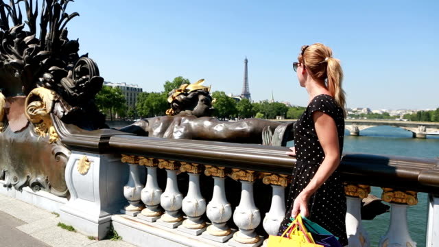 Young attractive woman holding shopping bags in Paris video