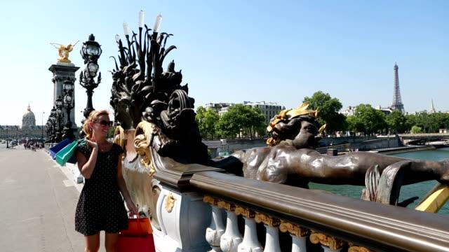vídeos de stock, filmes e b-roll de jovem atraente mulher segurando sacolas de compras em paris - moda parisiense