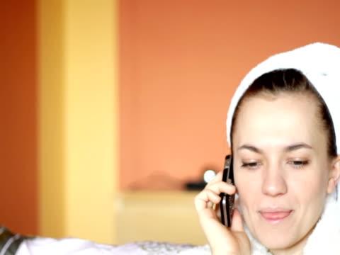 vídeos de stock e filmes b-roll de jovem mulher atraente em um roupão de banho falando no telefone celular - só mulheres jovens