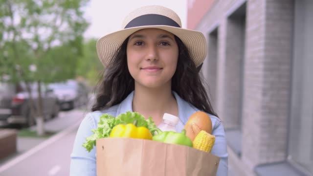 vídeos de stock, filmes e b-roll de uma mulher atrativa nova em um revestimento e em um chapéu da sarja de nimes carreg um saco de mantimento ao ter um bom modo e está sorrindo. close-up. 4k - sem glúten