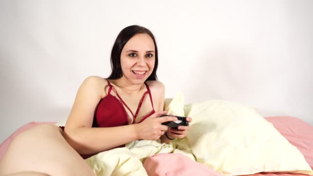 vídeos de stock e filmes b-roll de a young attractive woman in a lingerie plays a video game and loses. the woman decided to entertain herself with a big dildo in a bed on a white background - só mulheres jovens