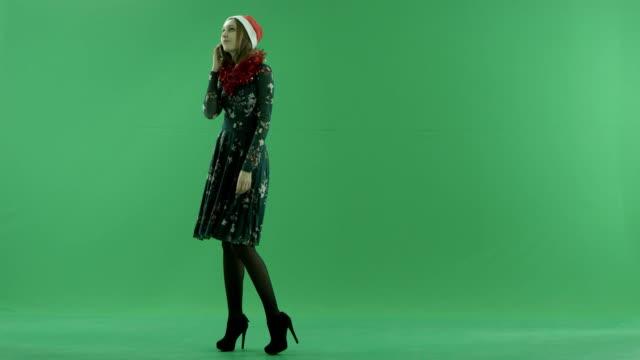 彼女の携帯電話は、背景にクロマキーを話し合ってクリスマス帽子の若い魅力的な女性 - サンタの帽子点の映像素材/bロール