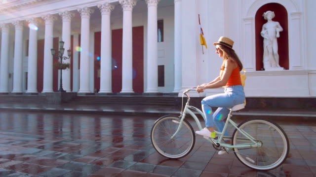vídeos de stock e filmes b-roll de young attractive woman in hat riding on vintage bike in city center and having some fun - bike emoji