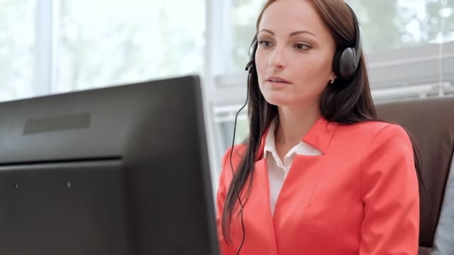 young attractive woman in red jacket sitting on desk at head of executive in red jacket. holds video conference in headphones with microphone. drinking coffee from white cup. - zestaw głośnomówiący filmów i materiałów b-roll