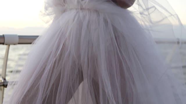 junge, attraktive frau im weißen ballett tutu stehen in der nähe von meer oder ozean bei sonnenaufgang oder sonnenuntergang licht. frau die füße in spitzenschuhen. aufnahmen von unten nach oben. das mädchen sieht in der ferne, über ihre brust mit ein - ballettröckchen stock-videos und b-roll-filmmaterial