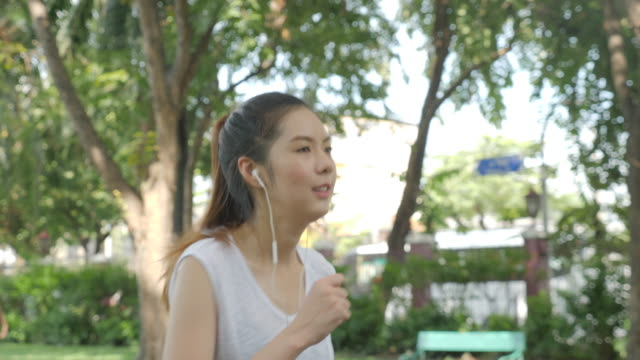 vídeos de stock e filmes b-roll de young attractive woman listening music in the earphone while running in the green city park. fitness running sport people and healthy lifestyle concept. - young woman running city