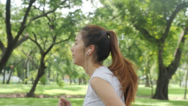緑の都市公園で中イヤホンで音楽を聴く若い魅力的な女性。フィットネス スポーツの人々 と健康的なライフ スタイルのコンセプトを実行します。 - ヘルシーなライフスタイル点の映像素材/bロール