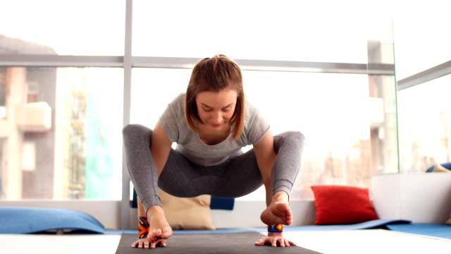 young attractive woman practicing yoga - posizione corretta video stock e b–roll