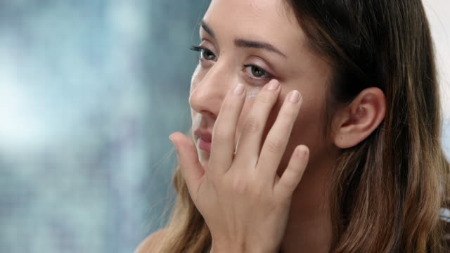 young attractive woman puts eye cream on her face - trattamento per la pelle video stock e b–roll