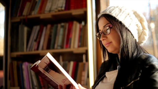 Young attractive woman reading a book video