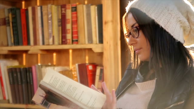 Young attractive woman reading a book,and resting in the beautiful day video