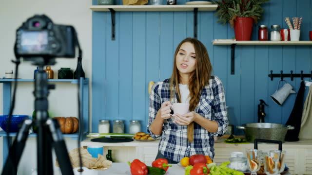 vídeos de stock, filmes e b-roll de jovem mulher atraente, gravação vídeo comida blog sobre culinária na dslr câmera na cozinha - blogar