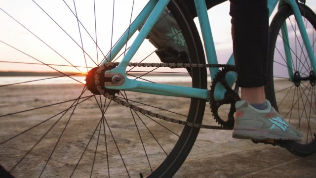 Young attractive woman riding biycle on the beach near the sea during sunset, slow motion, close up
