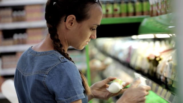 Young attractive woman selects a food at supermarket video