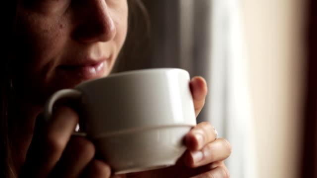 Jeune femme séduisante, assis près de la fenêtre et boire du thé - Vidéo