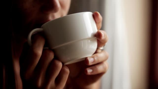 ung attraktiv kvinna sitter nära fönstret och dricka te - mellan 30 och 40 bildbanksvideor och videomaterial från bakom kulisserna