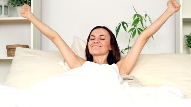 Young attractive woman stretching and yawning in bed video